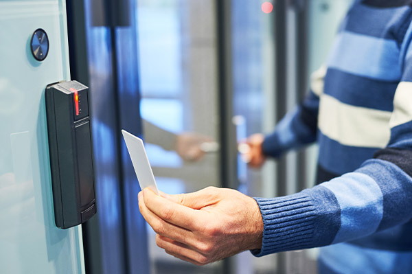Man using swipe card access panel to gain authorised access to the data centre