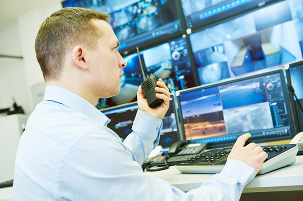 Data centre security guard monitoring surveillance system screens communicating with security team